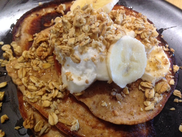 Pancakes topped with yogurt, banana and granola